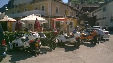 Eine Gruppe Motorradfahrer macht eine Pause am See.